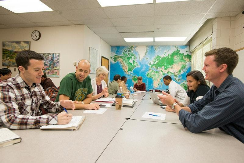 photo of a student discussion with a map in the background
