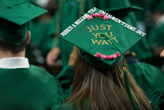"A Schar School student in a graduation gown and cap that says ""Just you wait"""